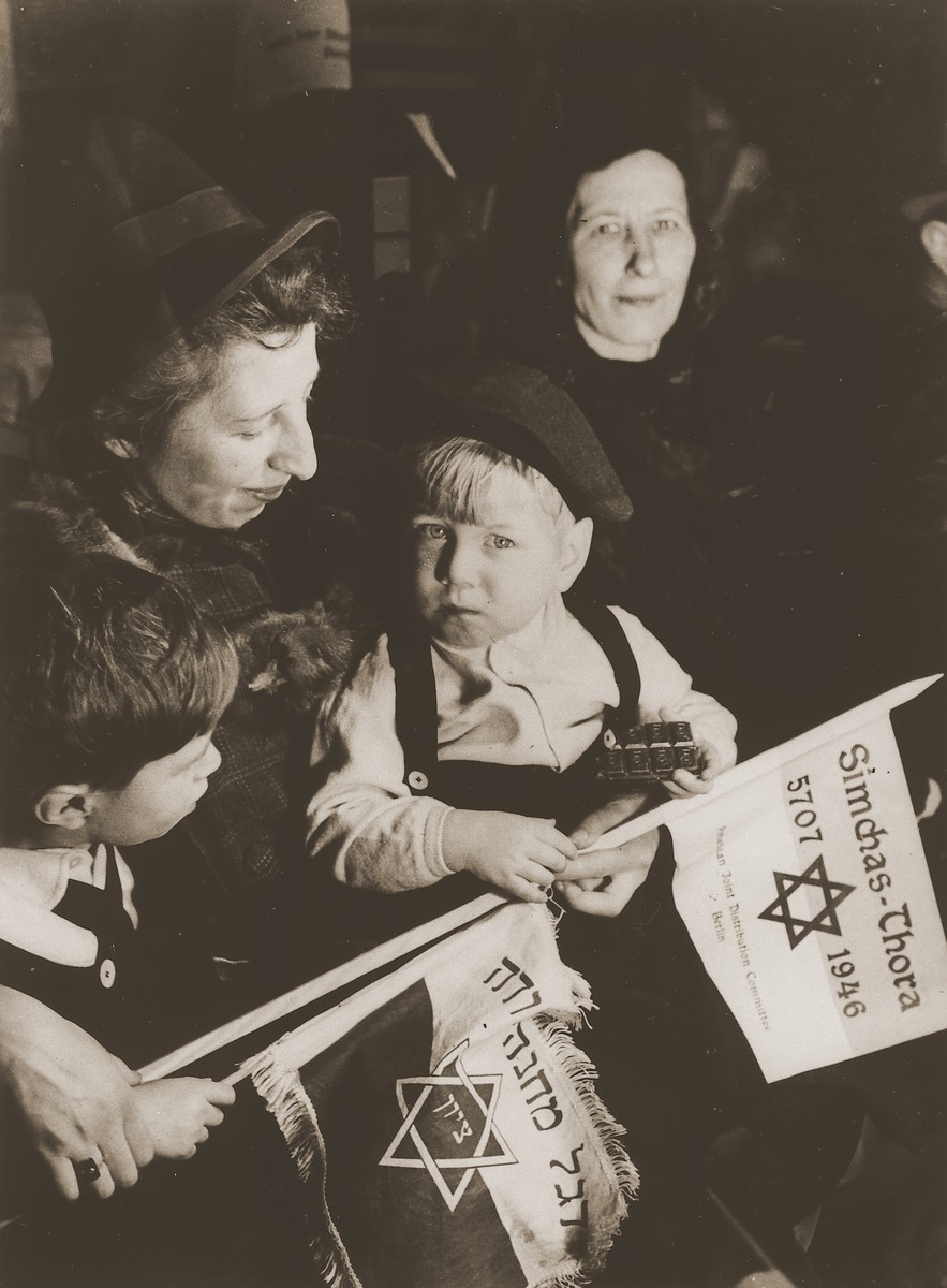 Two little boys holding toy flags attend a Simchat Torah celebration at the Schlachtensee displaced persons camp.