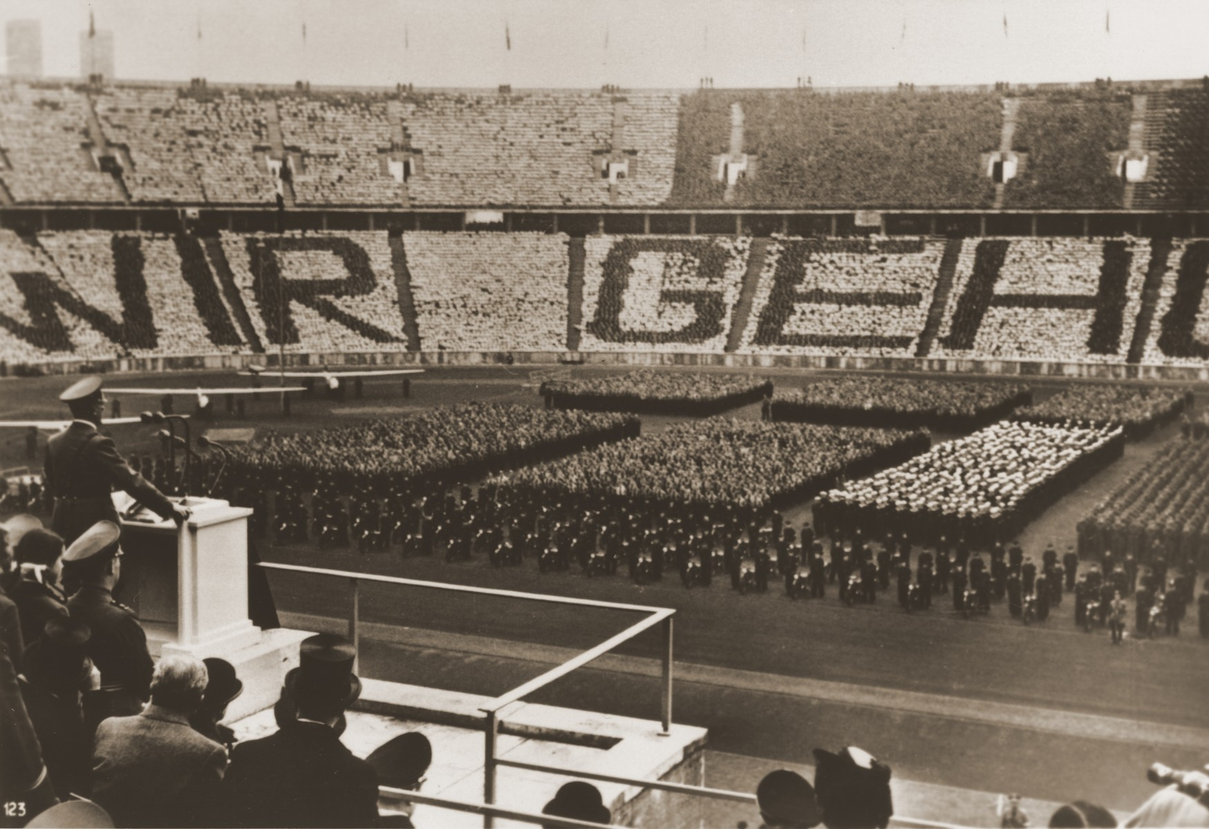 "Members of the BDM (Bund deutscher Maedels) stand in formation in the bleachers of the Berlin stadium to spell out ""Wir gehoeren dir!"" [We belong to you] while Adolf Hitler delivers an address at a rally held on the National Day of the German People (May Day)."