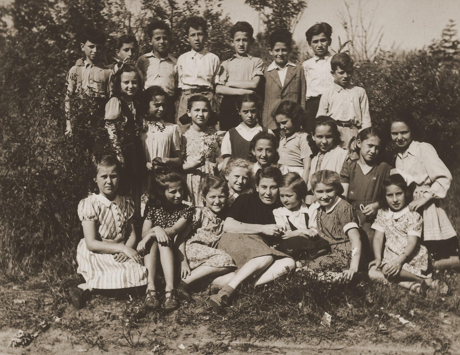 Sima Portnoy, a teacher at the Schlachtensee displaced persons camp, poses with her students outside.