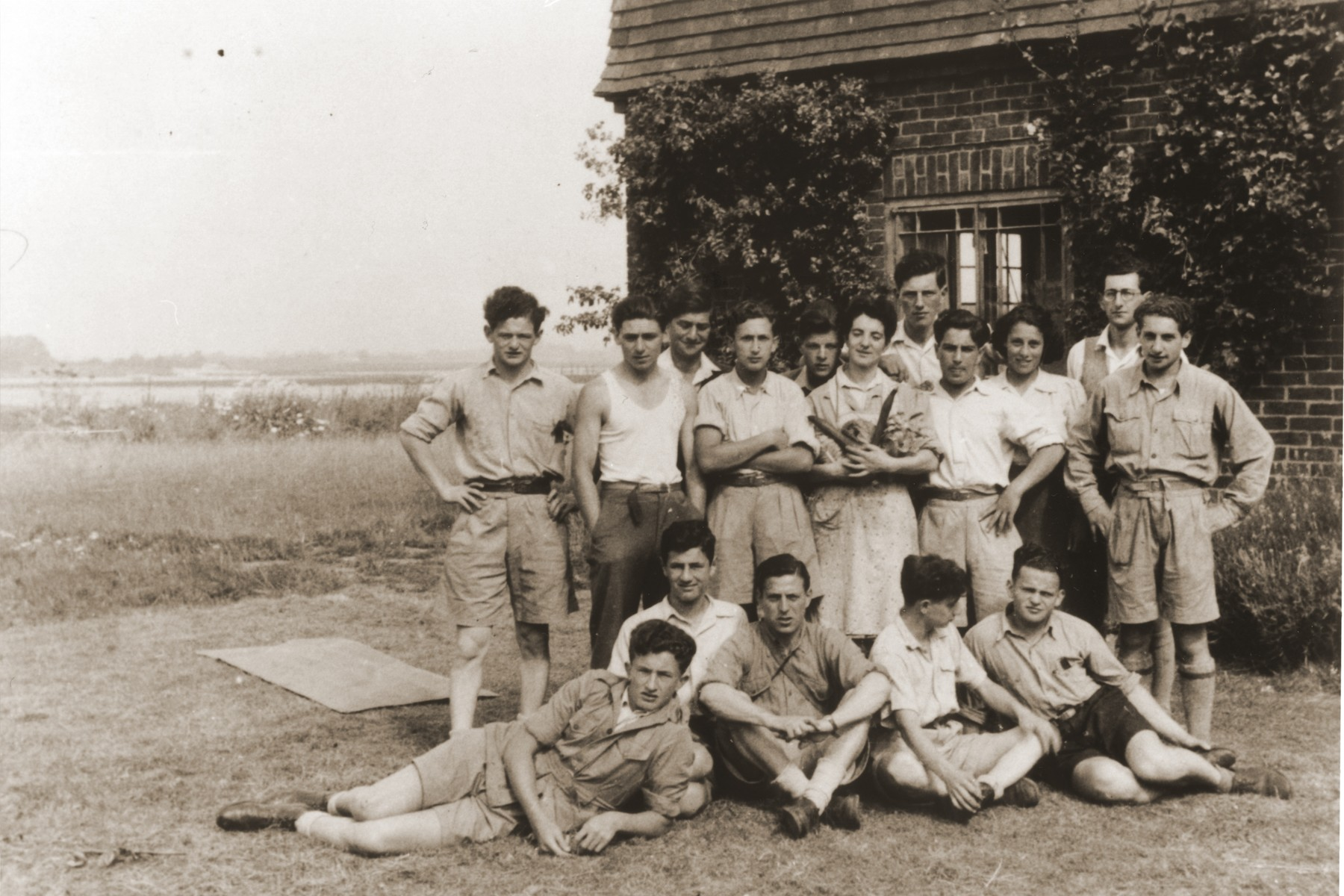 Jewish youth who came to England with the orphans transport pose at a kibbutz hachshara (Zionist agricultural collective) outside of London.  Among those pictured are Roman Halter (semi-reclining, far left), Ben Helfgott (semi-reclining far right) and Moniek Goldberg standing far left.