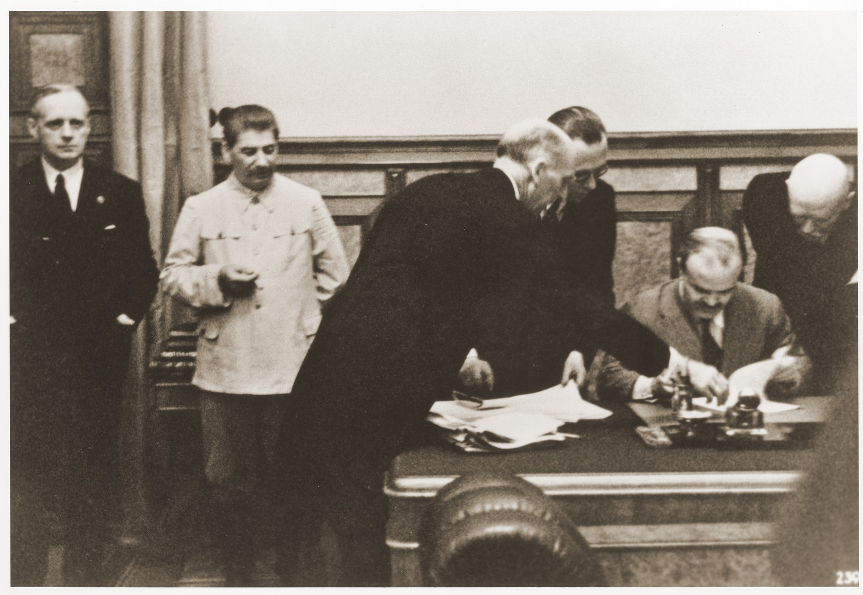 Soviet foreign minister Vyacheslav Molotov (seated) signs the Nazi-Soviet Non-Aggression Pact in Berlin.    Standing (from left to right) are: Joachim von Ribbentrop; Joseph Stalin; German Undersecretary of State Gauss; German Legate Hilger; and Ambassador Graf von Schulenburg.