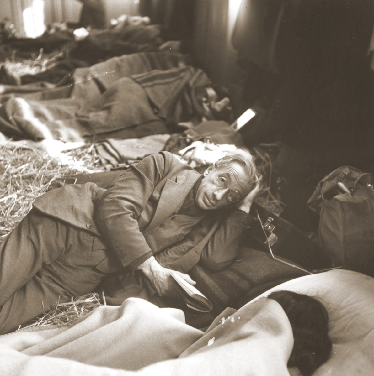A elderly Jewish man rescued from Theresienstadt rests on a bed of straw in the Hadwigschulhaus in St. Gallen.