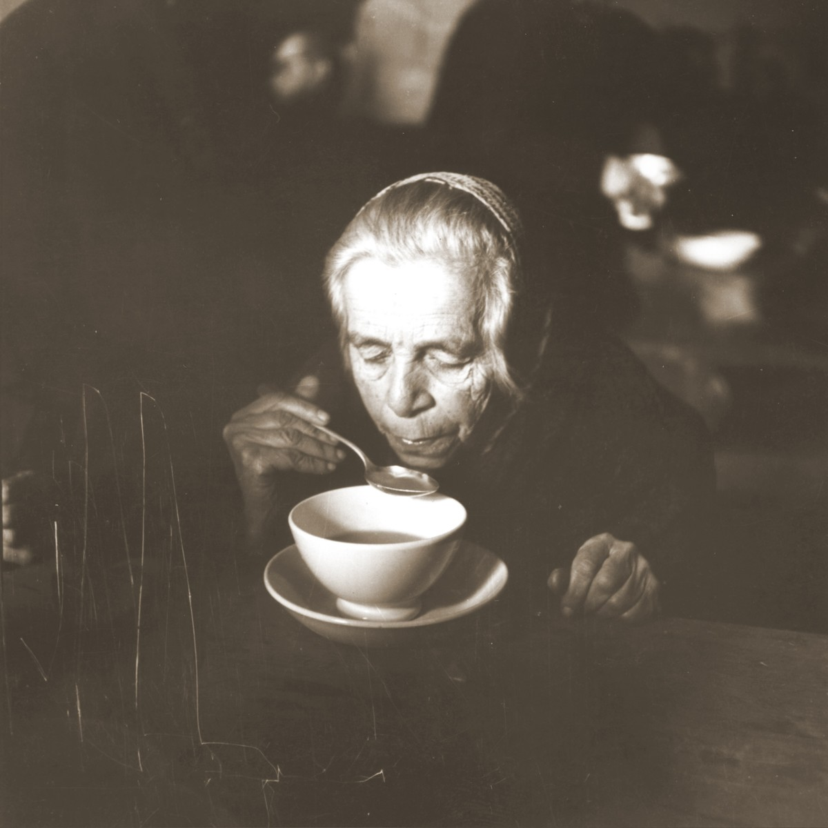 An elderly Jewish woman rescued from Theresienstadt  eats a warm meal in the Hadwigschulhaus in Saint Gallen.
