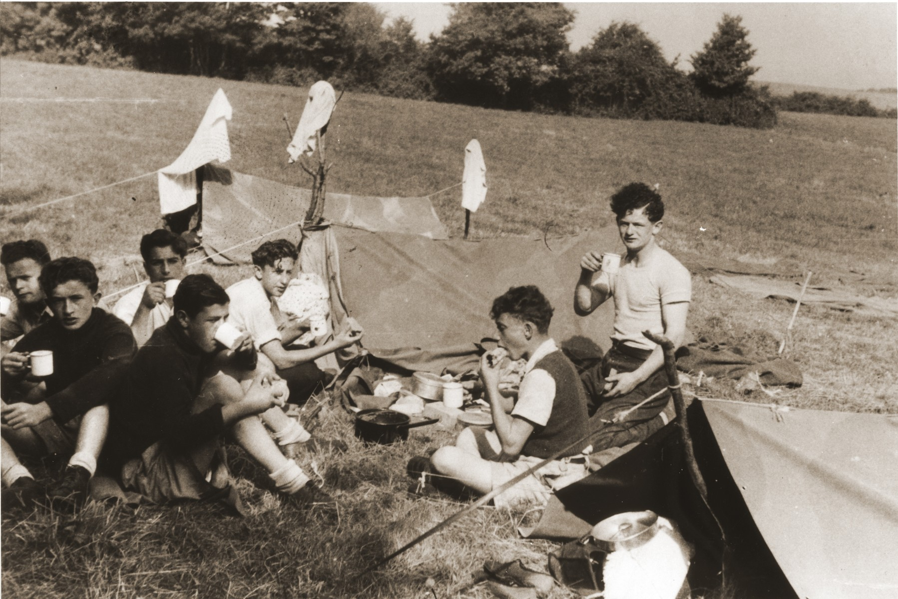 Members of the orphans transport to England go camping on the Isle of Wight.  Among those pictured are Paul Gast (center), Szlomo Kuszerman (second from the right) and Moniek Goldberg (right).