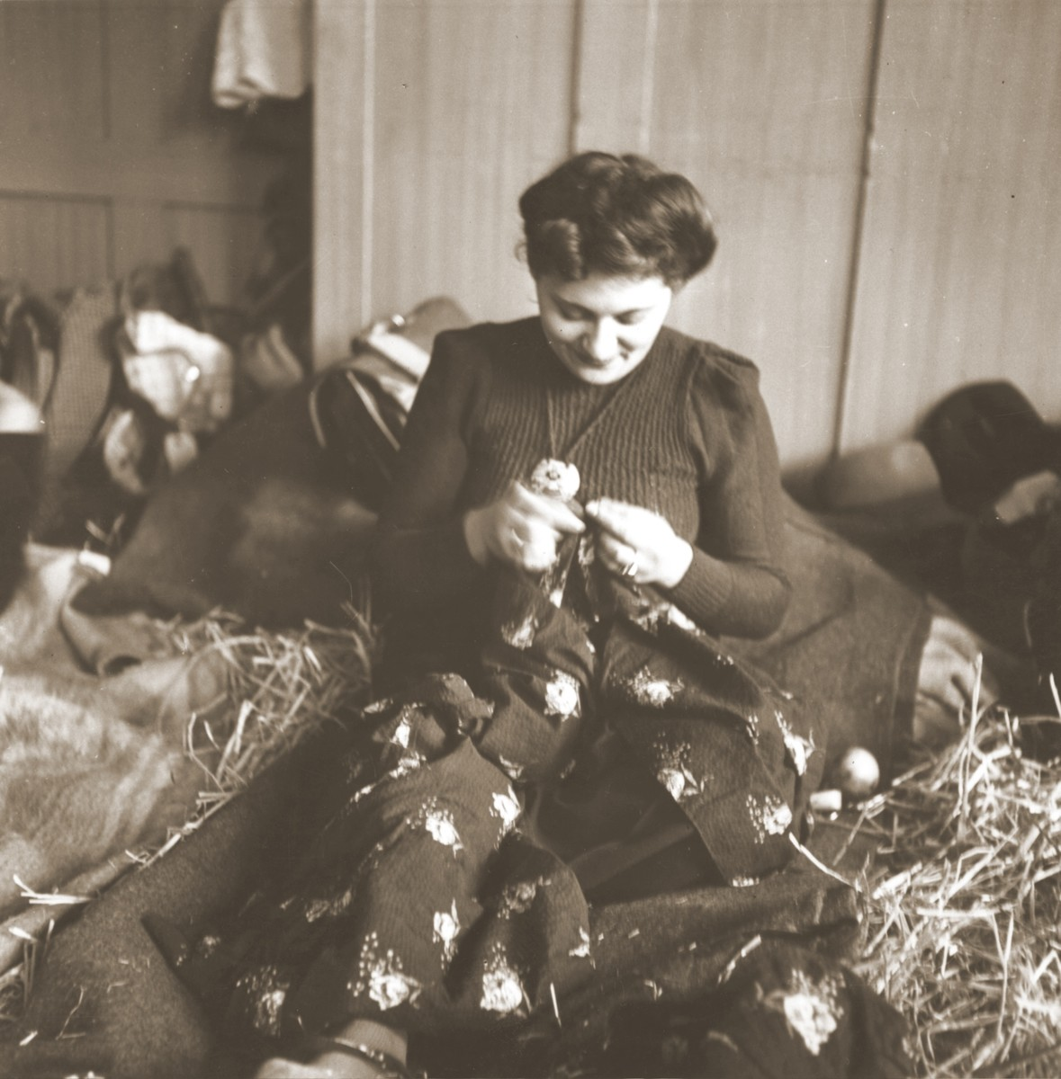 A Jewish woman rescued from Theresienstadt mends her clothing in the Hadwigschulhaus in St. Gallen.
