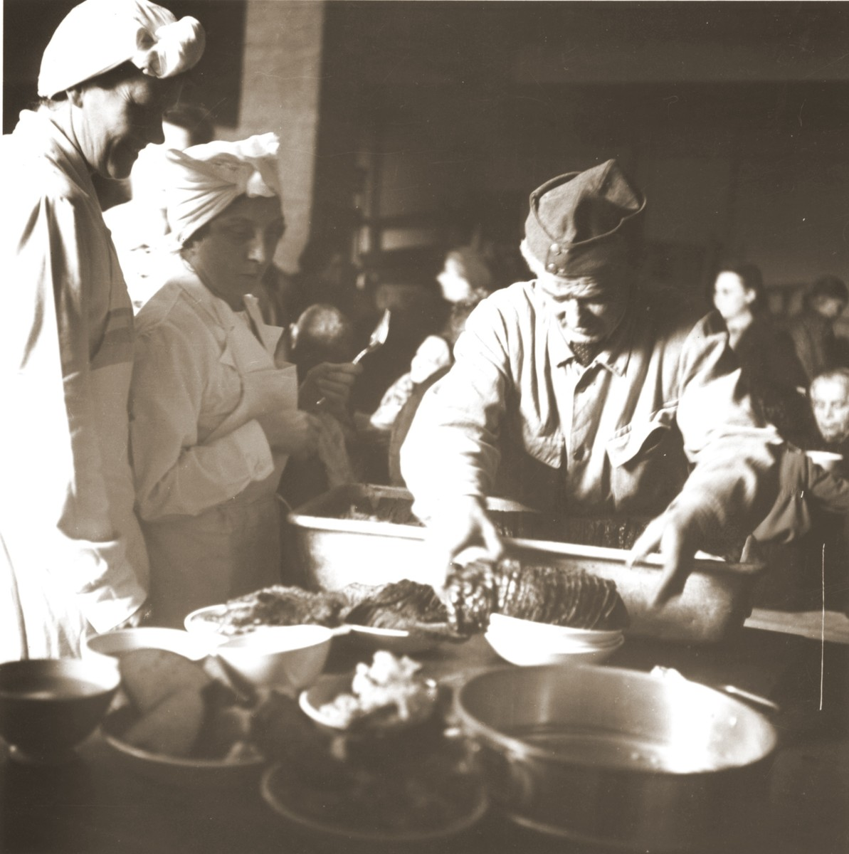 Swiss Red Cross workers and military reservists prepare a meal for Jews rescued from Theresienstadt.