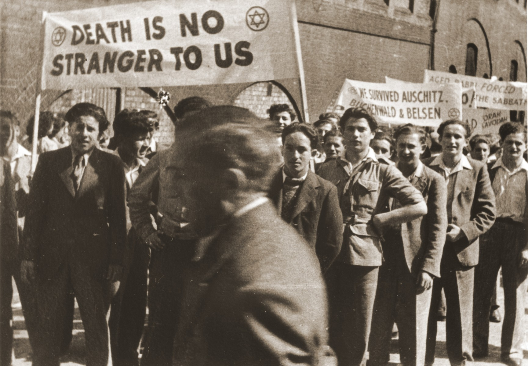 "Jewish youth who were brought to England on the orphans transport after the war protest against British policy in Palestine at a demonstration in Trafalgar Square, London.  The young men carry banners that read ""Death is no stranger to us"" and ""We survived Auschwitz, Buchenwald and Belsen"".  Moniek Goldberg is on the far right.  Also pictured are Harry Bolsum, Joel Renz and Jonny Fox."