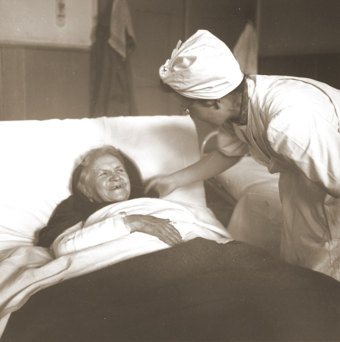 An elderly Jewish woman rescued from Theresienstadt  receives medical attention from a Swiss Red Cross worker in the infirmary of the Hadwigschulhaus in St. Gallen