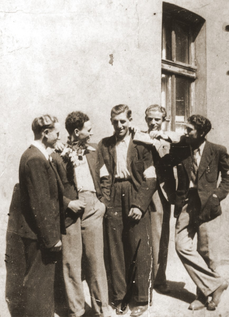 A group of friends gather outside a house in the Bedzin ghetto.  Standing from left to right are Abraham Faymann, Moniek Bronner, Motek Faymann, unknown, and Moniek Klugman.