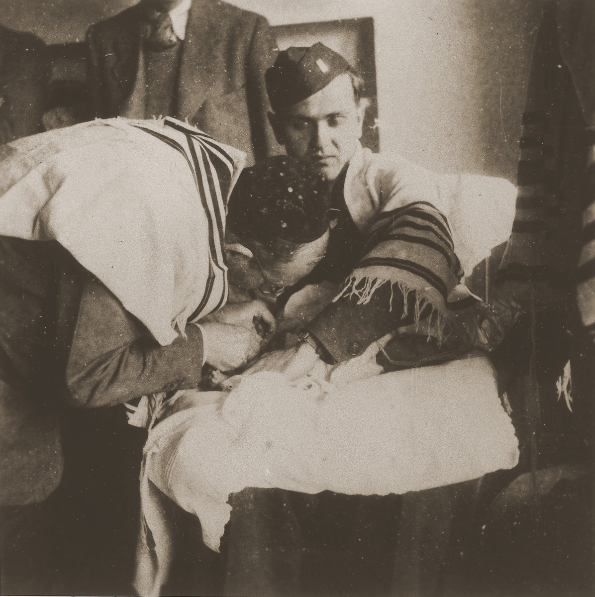 Chaplain Mayer Abramowitz holds a newborn during a circumcision ceremony at the Schlachtensee displaced persons camp.