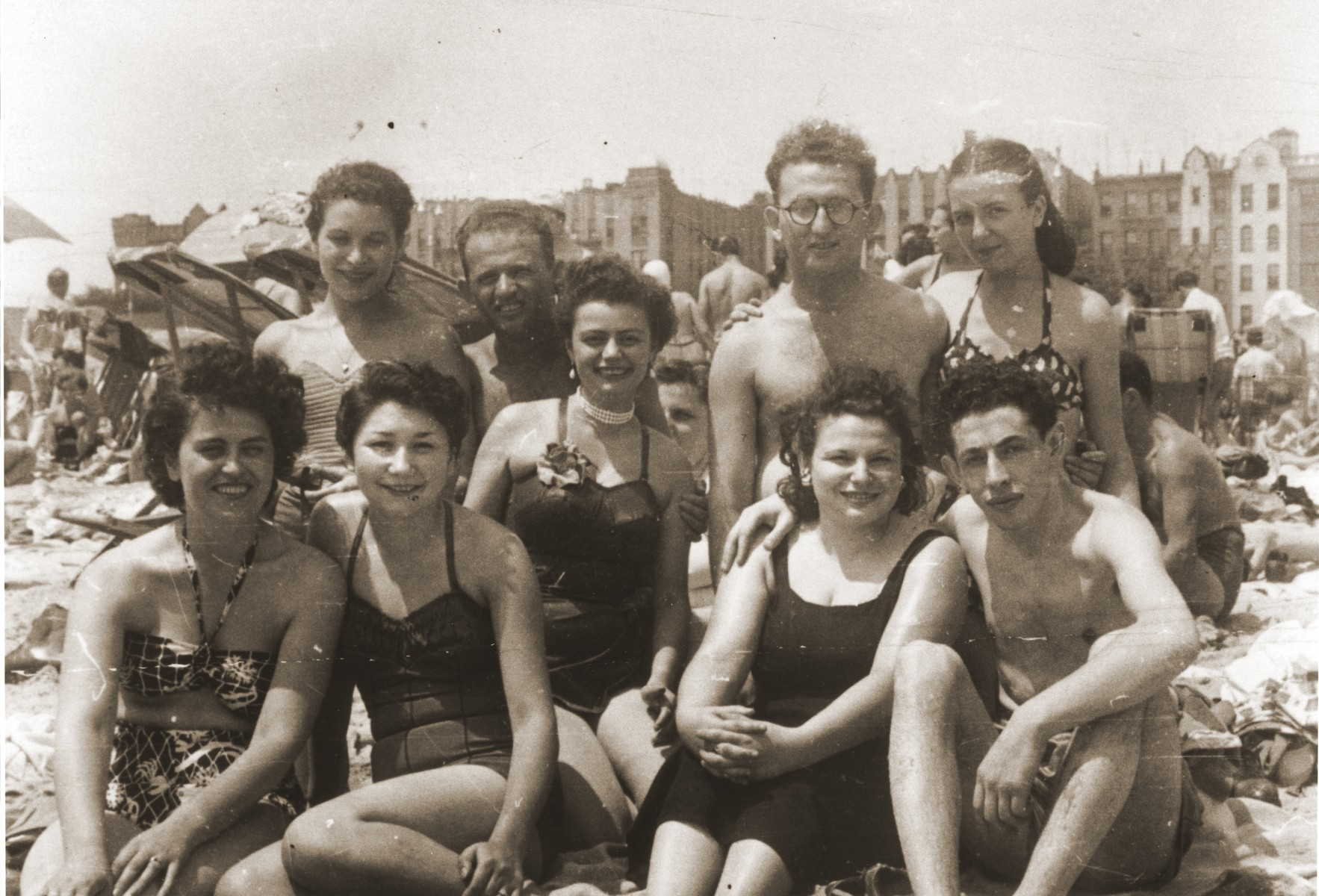 Young Jewish men and women who came to England with the orphans transport relax on the beach.  Pictured in the back row, from left to right are, Lillie Moskovich, Willie Zelovic, Erica Grossman (center wearing a necklace), Hershel and Renate Zelovic.  In the front row, from left to right are, Paulette, Elizabeth Weiss, and Ibi and Willie Rosenberg.