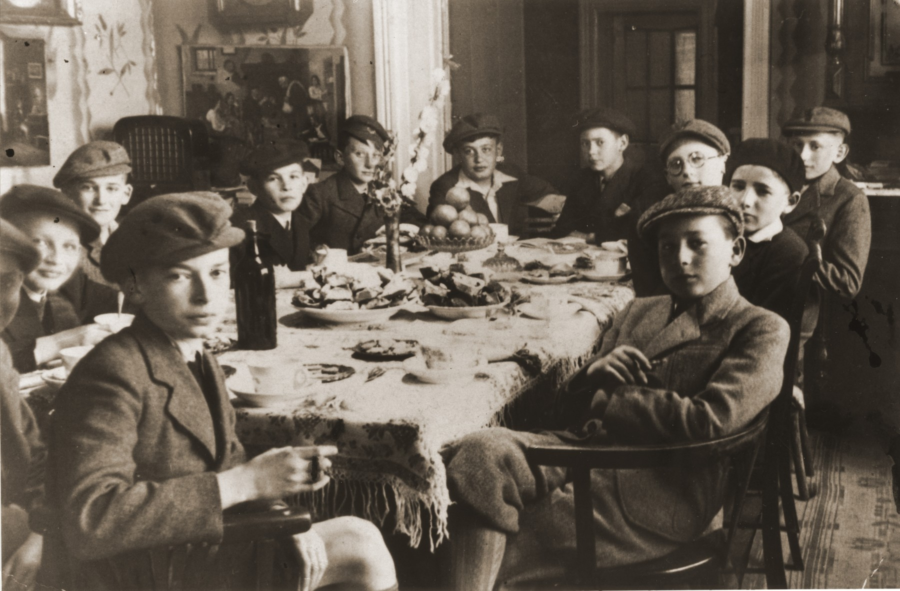 Robert Vermes (at the back head of the table, third from the right) entertains a group of friends at a bar mitzvah party in his home in Topolcany, Slovakia.  Almost all of the boys were killed during the war.