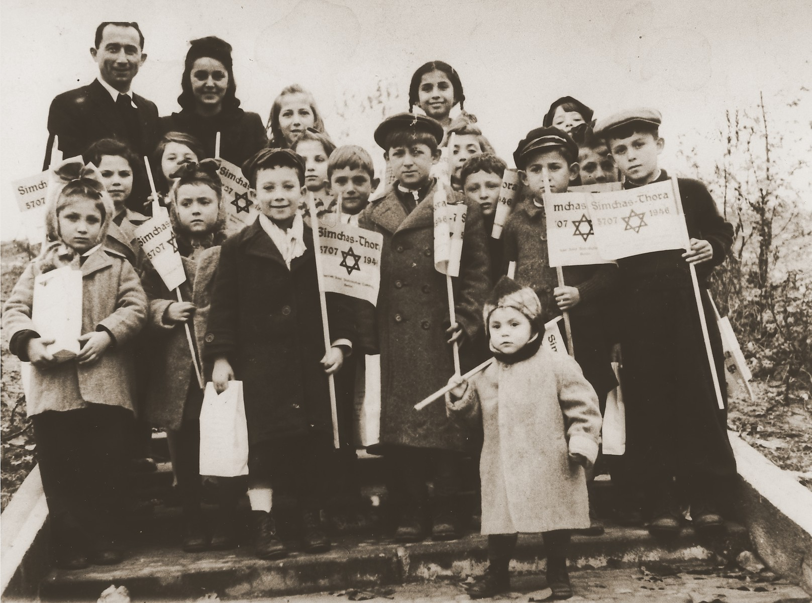Group portrait of children holding toy flags for Simchat Torah at the Schlachtensee displaced persons camp.  Among those pictured is Rachel Kosowski (top row, second from the left).