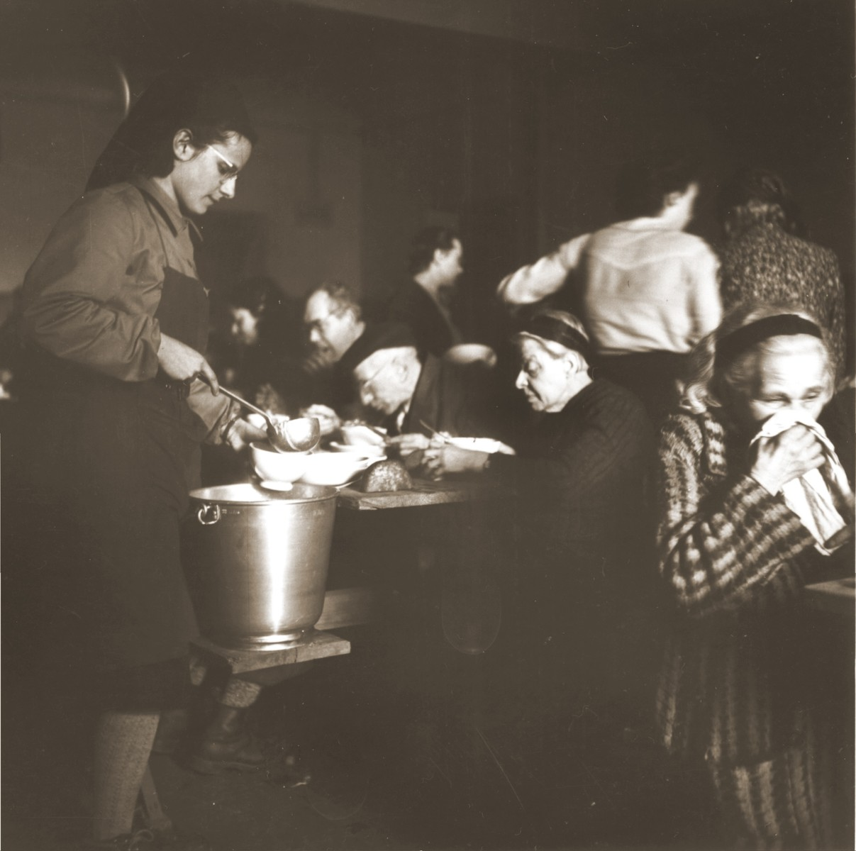 Swiss Red Cross workers distribute food to elderly Jews rescued from Theresienstadt in the Hadwigschulhaus in St. Gallen.