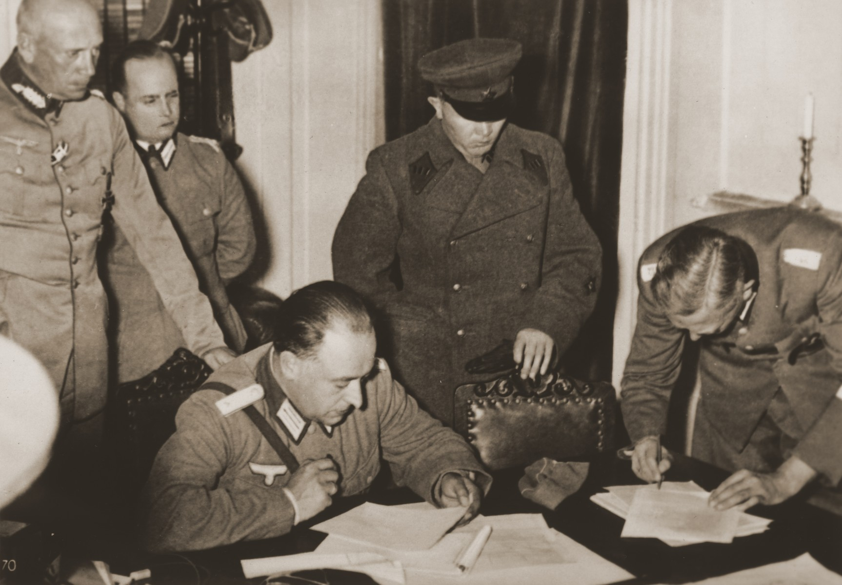 """German and Soviet military officers sign the agreement by which Poland is partitioned between Germany and the Soviet Union.  Original caption from Corbis-Bettmann reads:  """"A scene in the government building here as German (left) and Soviet (right) army officers divided Poland into two sections.  A demarcation line cut the country from North to South, with Germany occupying the territory west of the line, and Russia the east."""""""