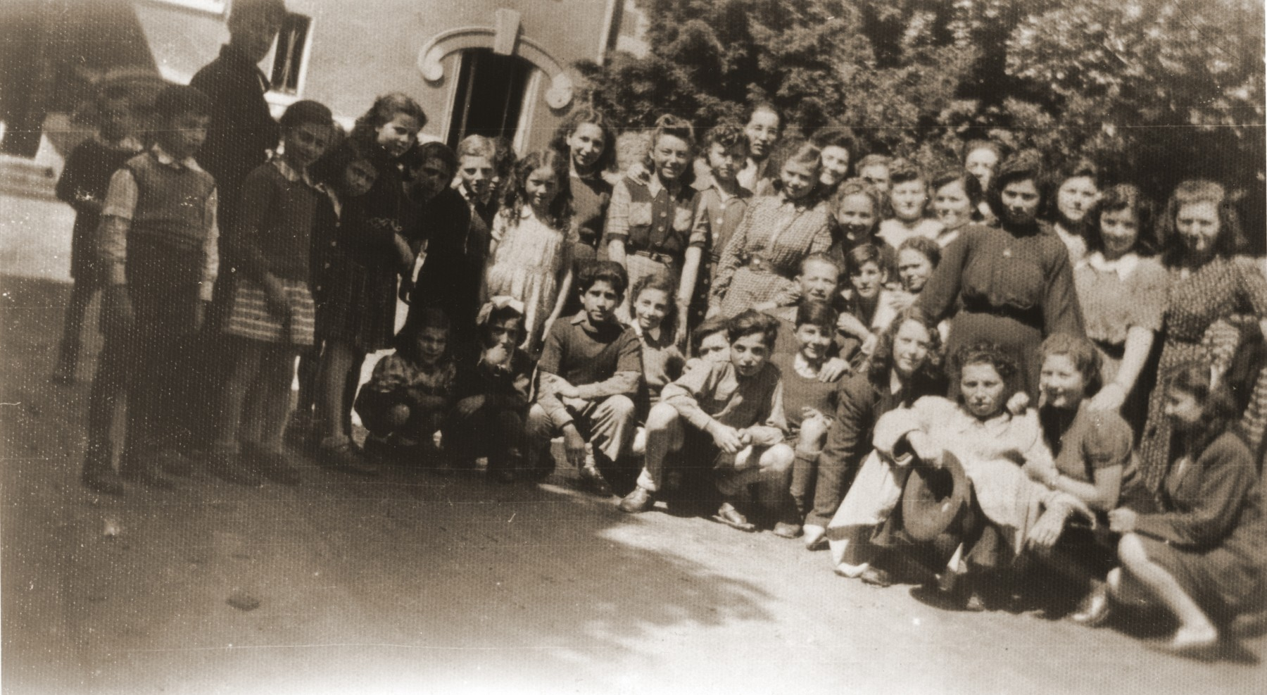 Group portrait of members of the orphans transport during their sojourn in France on their way to England.  Among those pictured are S. Lampert, Mermelstein, E. Zelovic, Vermes, Markovits, Weinberger, M. Lampert, W. Zelovic, Weiss, Davidovic, Lebovic, Slomovic, Birnbaum, Zelikovic and Bohm.