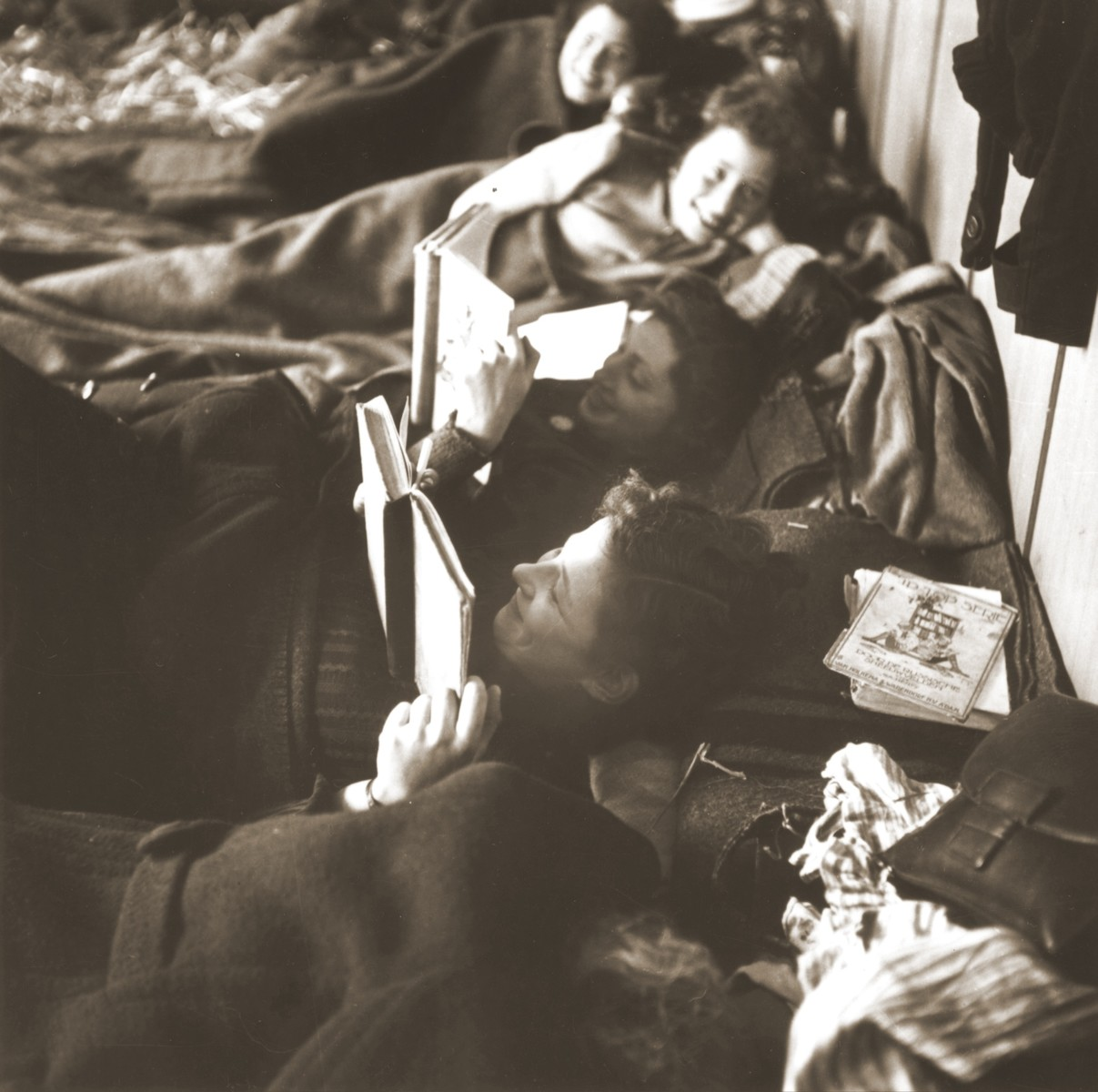 Jewish women rescued from Theresienstadt read while resting on their beds of straw in the Hadwigschulhaus in St. Gallen.