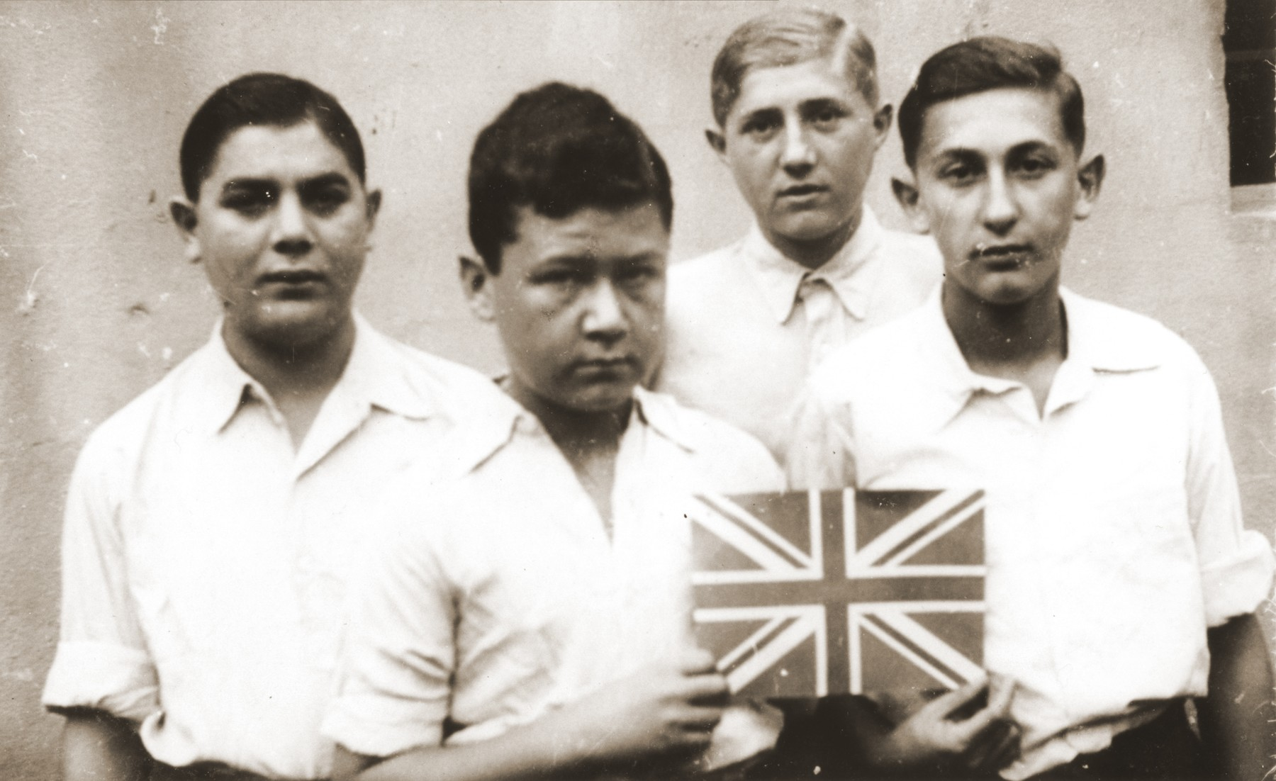 Four members of the orphans transport pose with a Union Jack soon after their arrival in England.  Among those pictured are Polek Gastfreund (right); Jerry Herszberg (second from the left); and Felix Berger (left).