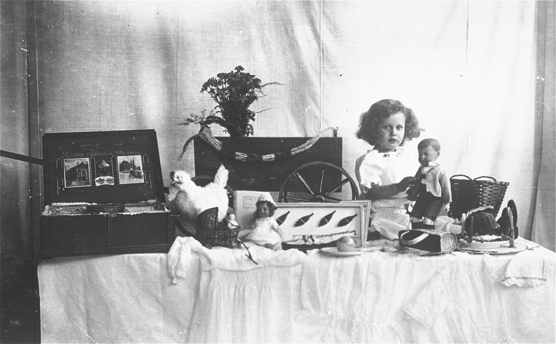 Marianne Anker plays with a doll on a table laden with gifts for her birthday.  Marianne (b. 1913) was the oldest daughter of Leo and Lisel (Pfeiffer) Anker.