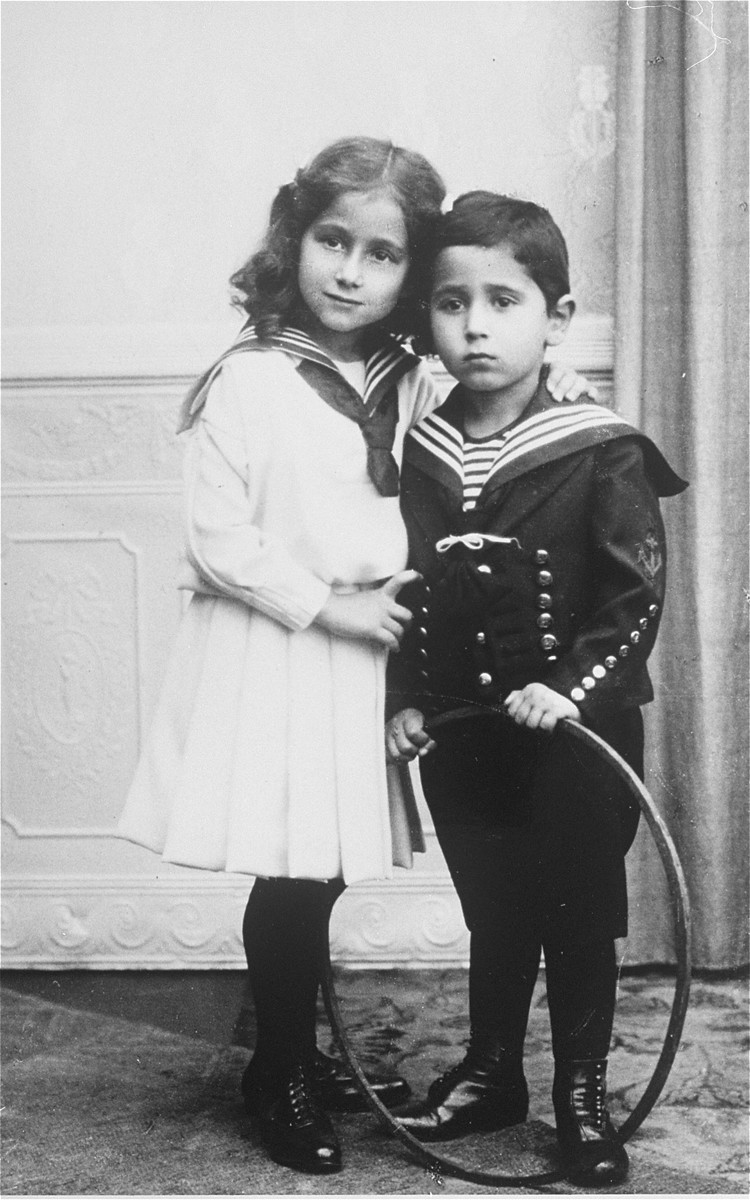 Studio portrait of Jewish siblings holding a hoop.  Pictured are Lotte Hirschberg (b. 1902) and her brother, Ernst (b. 1903).  They are the children of Dora and Hugo Hirschberg of Danzig.