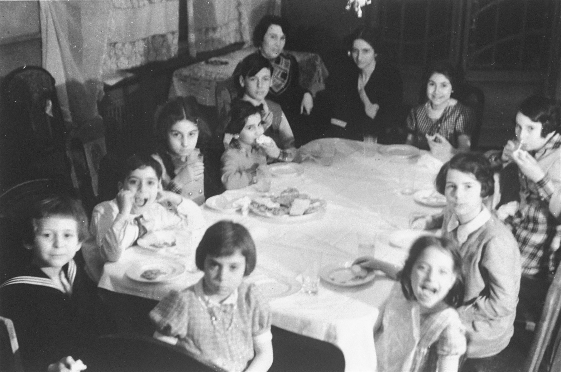 Children seated around a table at a birthday party for Eva Anker at her home on Klopstockstrasse 17 in Berlin.   Pictured clockwise from the bottom left are: Theo Olof (?); Heinz Karplus (cousin), Dodi Anker, Hilda  Anker, Klaus Loewald, Olga Jacobson, Gertrud Anker, Hannele Ephraimsohn, Eva Anker, Annelise Lowald, Else Karplus (cousin) and Hanna Jacobson (friend).