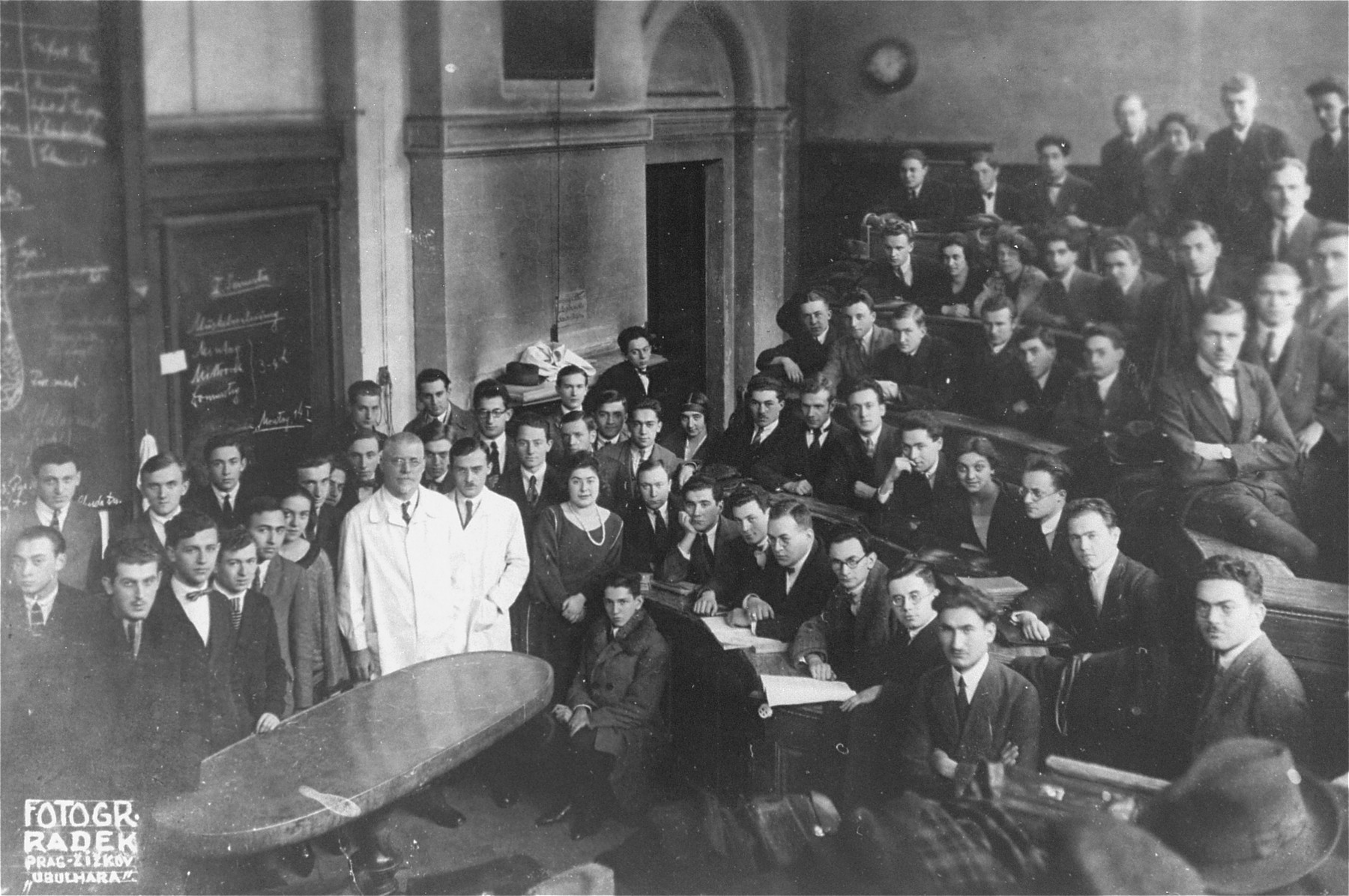 A class of medical students pose in a lecture hall at the Charles University in Prague.  The older gentleman wearing a white coat has been identified as Prof. Otto Grosser, the head of the Institute of Anatomy.