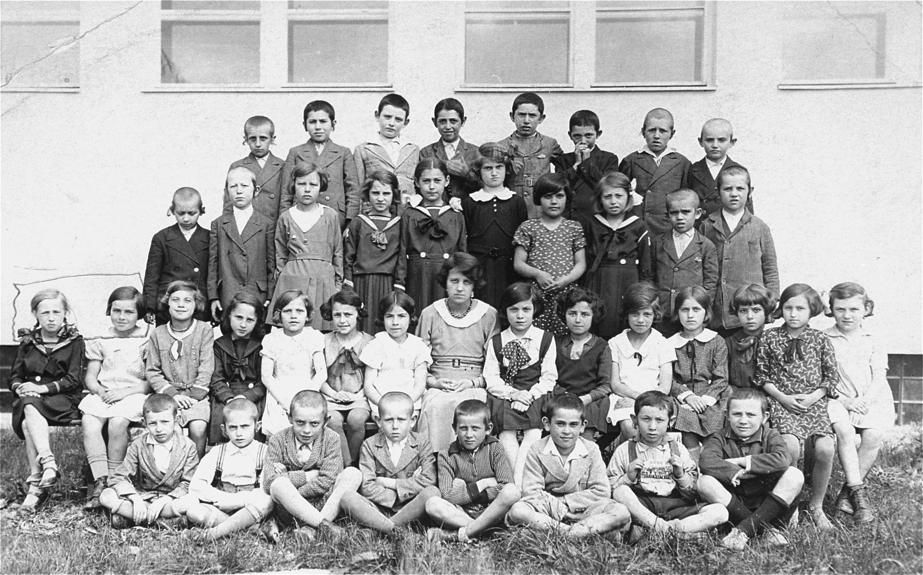 Group portrait of second grade students and teachers at a Czech Jewish school in Vinogradov, Ukraine.    Among those pictured are Dwajri (Deborah) Rottenstein (second row, first from the left), and her cousin Gitta Busch (next to her).  Dwajri is the sister of donor Edith Rottenstein Gross.  Dwajri perished at the Stutthof concentration camp.  Gitta was shot and killed by a German soldier in 1945.
