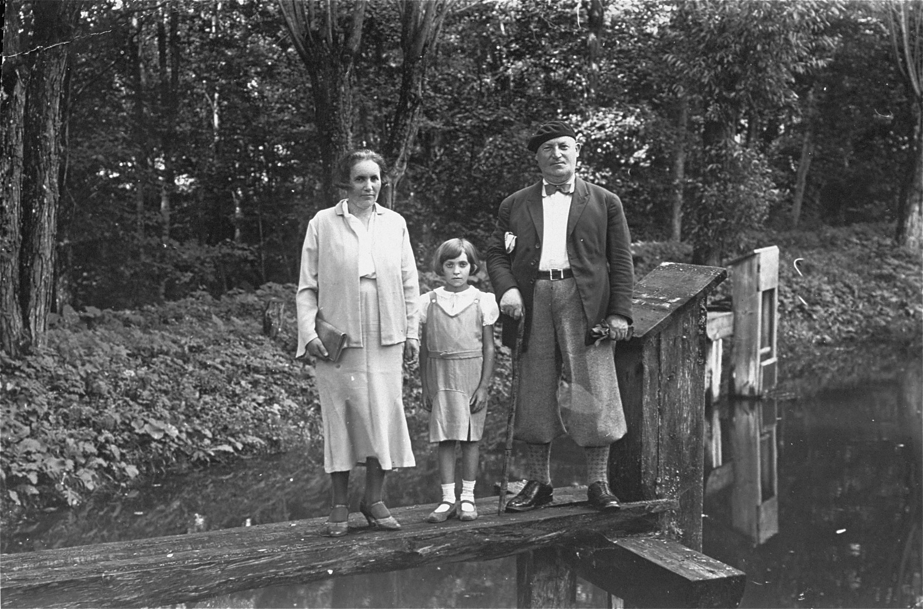 Jewish opera singer, Leo Kaplan, poses with his wife and daughter in a park.  Kaplan performed with the Berlin opera in the interwar period.  He was the cousin of the donor's father.