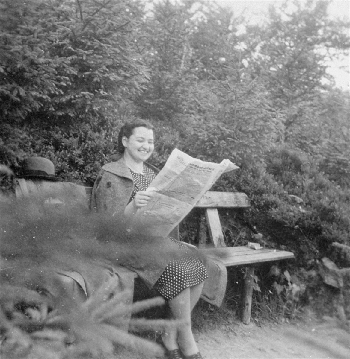 Portrait of the donor, Magda Herzog Muller, reading a newspaper on a park bench in the Czech resort of Trencianske-Teplice.