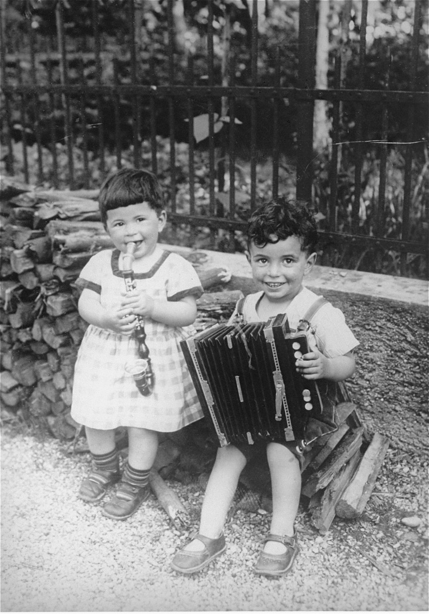 Liese and Siegbert Fischer playing toy instruments in the backyard of their home in Augsburg, Germany.  Both were sent on a Kindertransport to England in July 1939.