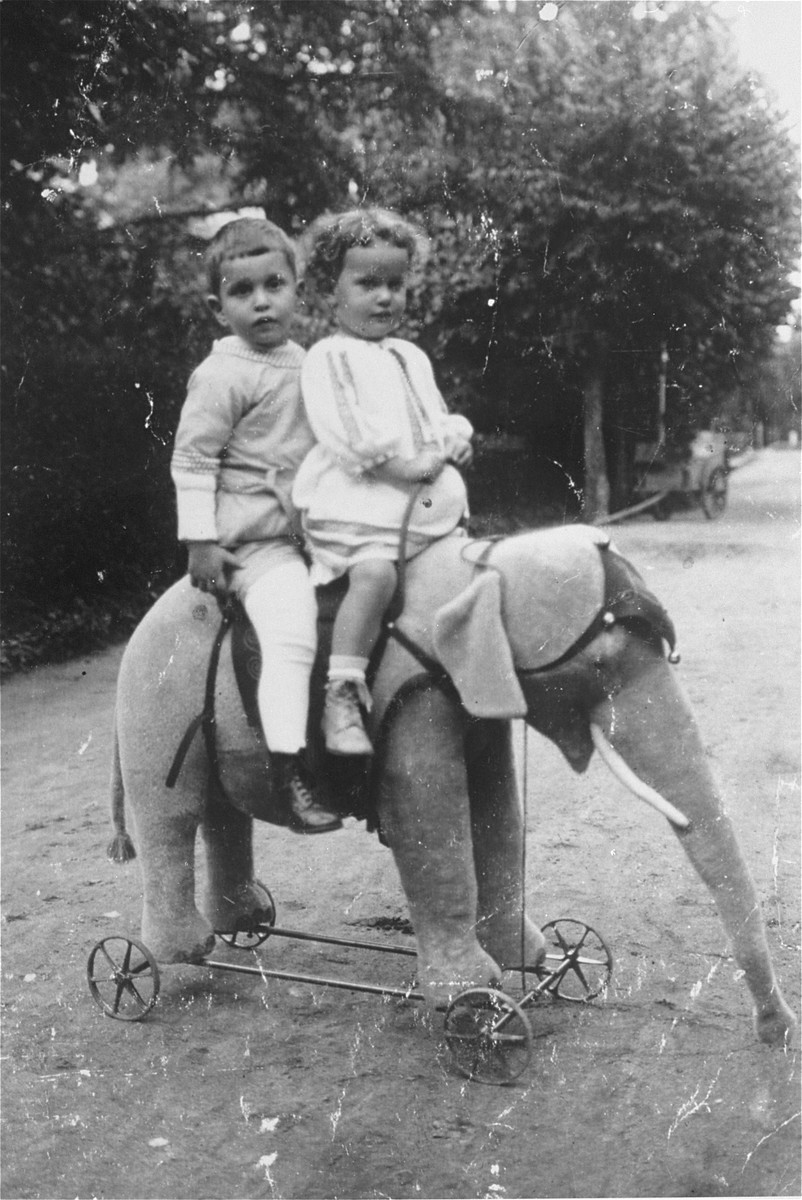 Herbert Anker (b. 1912) rides on a toy elephant with his cousin, Marianne Anker (b. 1913).
