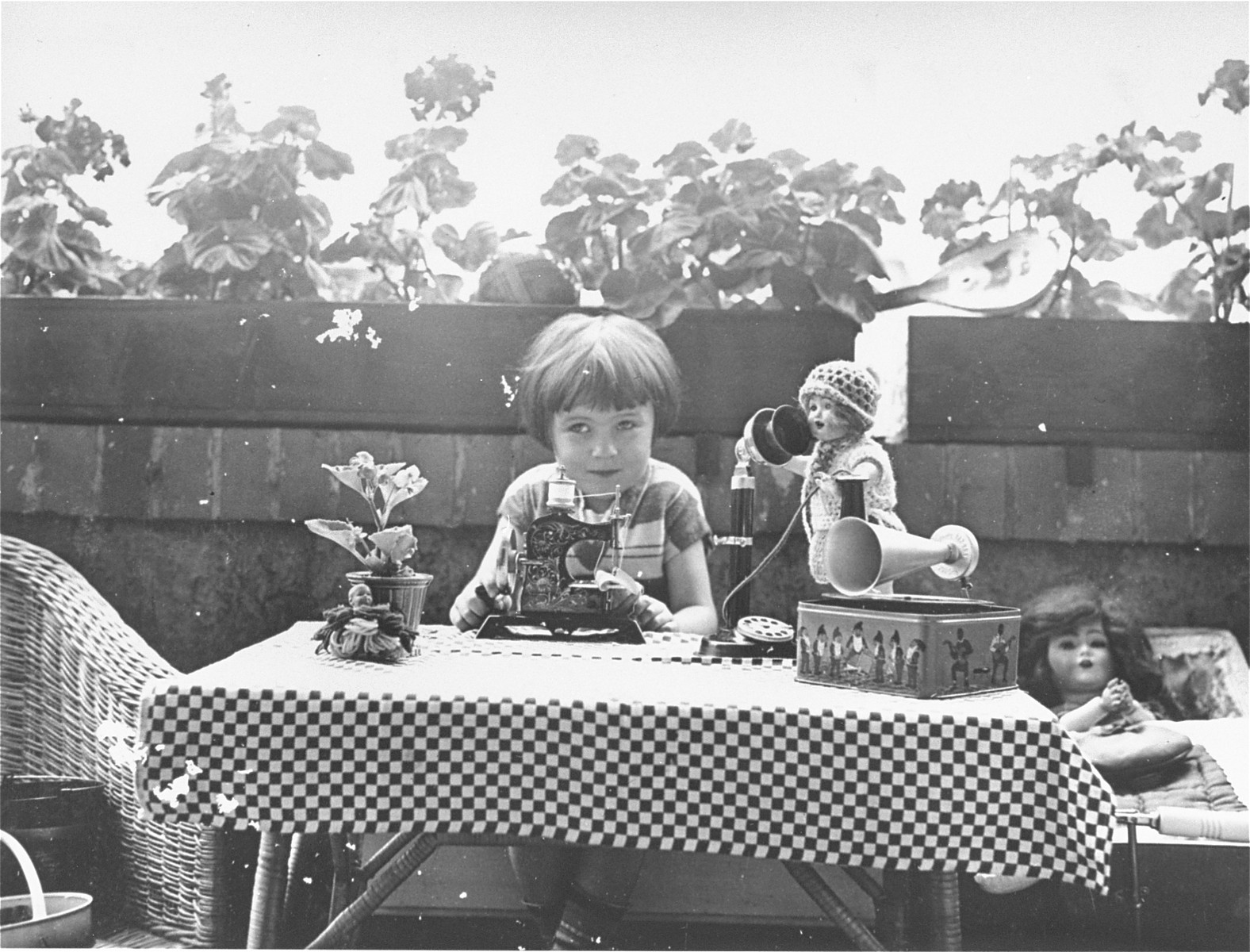 A young Jewish child sits at a table full of toys on the terrace of her home in Leipzig.  Pictured is Berta Rosenheim, who as a teenager was sent to England on a Kindertransport.