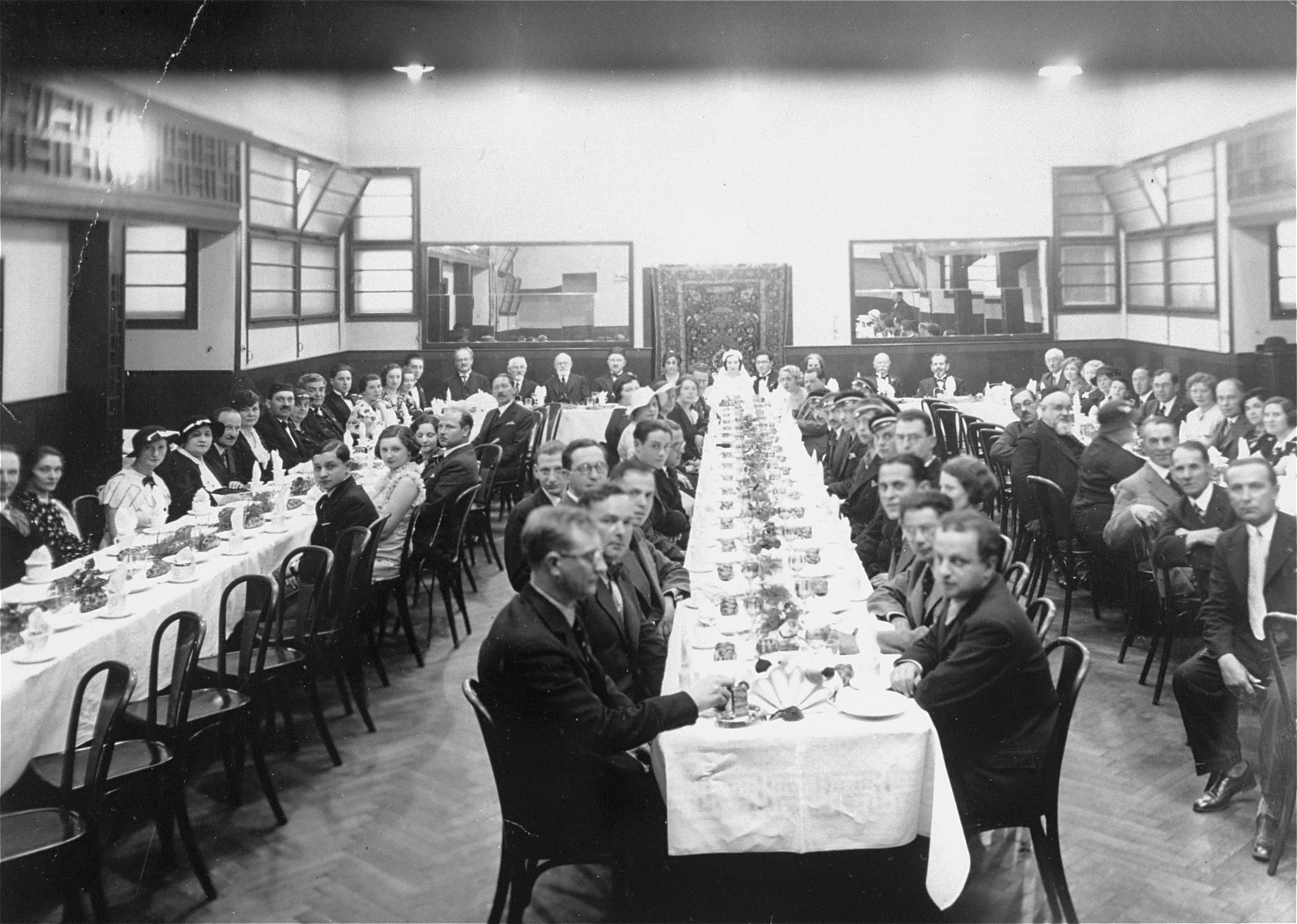 "The wedding reception of Ruth Kohn (b. 1916) and Ludwig Kleinberg at the Cafe Asherman (Beit Haam) in Prague.   Members of a Zionist student organization, the ""Barisia,"" identified by their distinctive caps, are seated on the right side of the center table.  Among those pictured, at the middle table on the right, is Jan Low,  the editor of the weekly paper Der Judenstaat in Prague."