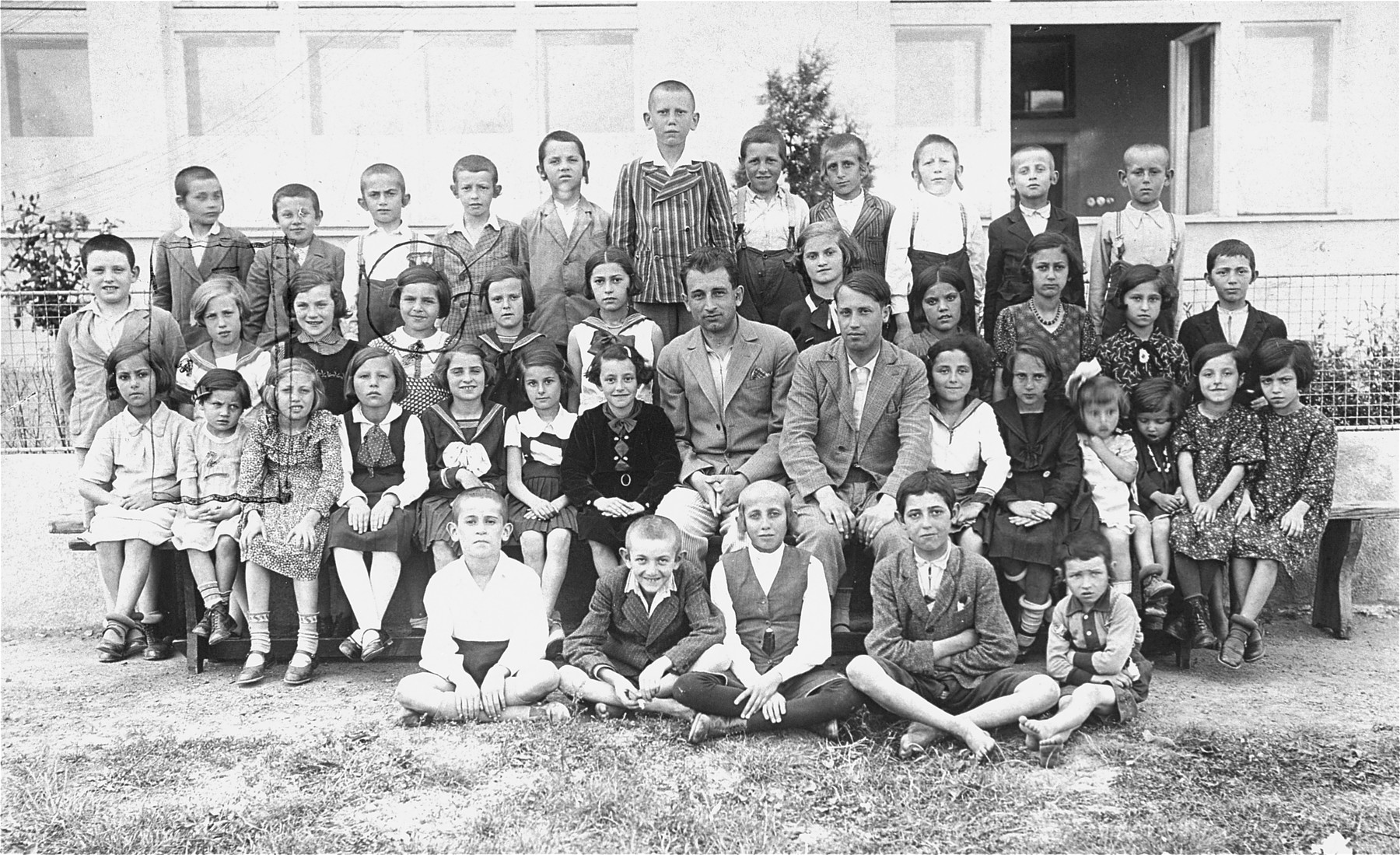 Group portrait of second grade students and teachers at a Czech Jewish school in Vinogradov, Ukraine.    Among those pictured are Edith Rottenstein (second row, second from the left), Dwajri (Deborah) Rottenstein (third row, second from the left), and her cousin Gitta Busch (third row, fourth from the right).  Dwajri is the sister of donor Edith Rottenstein Gross.  Edith survived the Auschwitz and Stutthof concentration camps.  Dwajri perished at the Stutthof concentration camp.  Gitta was shot and killed by a German soldier in 1945.  The boy in the back row, eighth from the left, may be Isidor Goldberger.