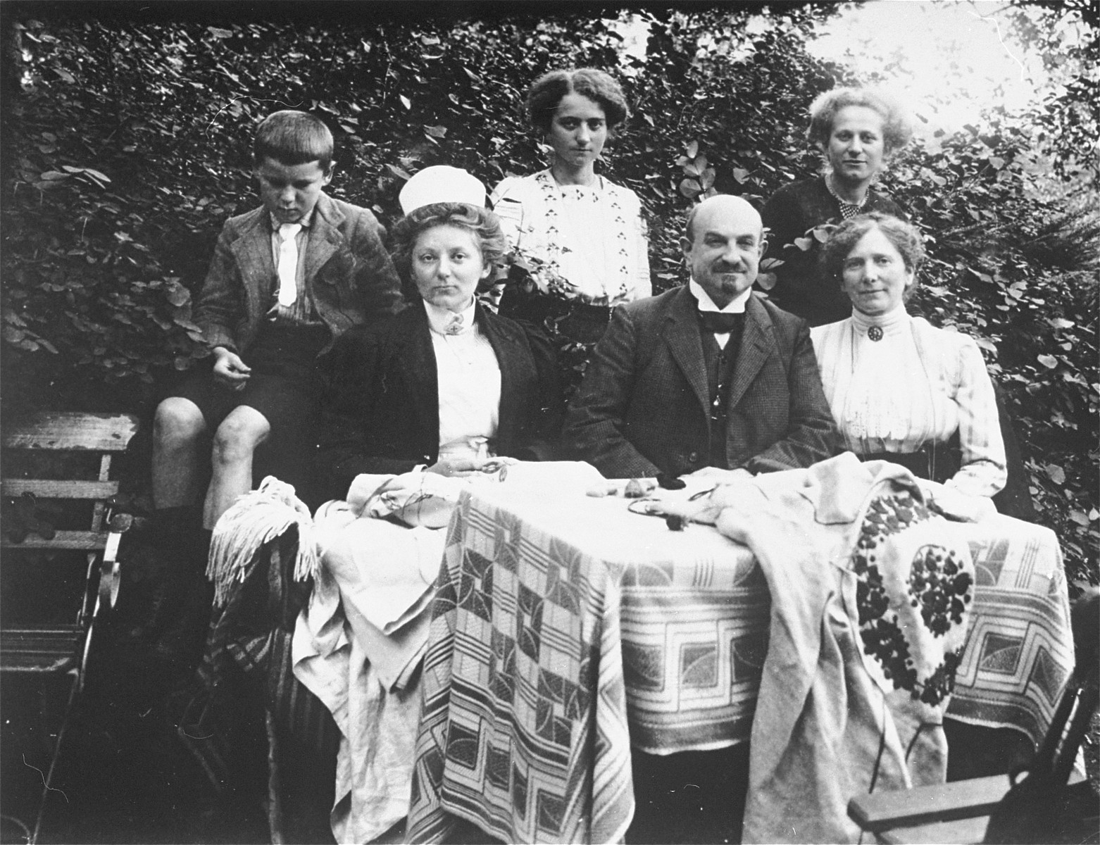 Members of the Gottschalk family sit at a table in the yard of their home in Schlawe, Germany.    Among those pictured are Gertrud Gottschalk (top row, second from the left; Kaethe Gottschalk (top row, third from the left).  Hugo and Bertha Gottschalk (seated at the right).