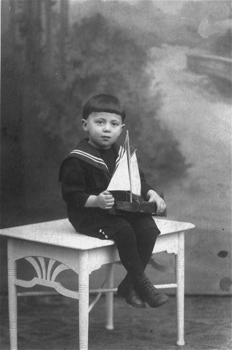 Studio portrait of Abraham Moshe Muhlbaum holding a toy boat.