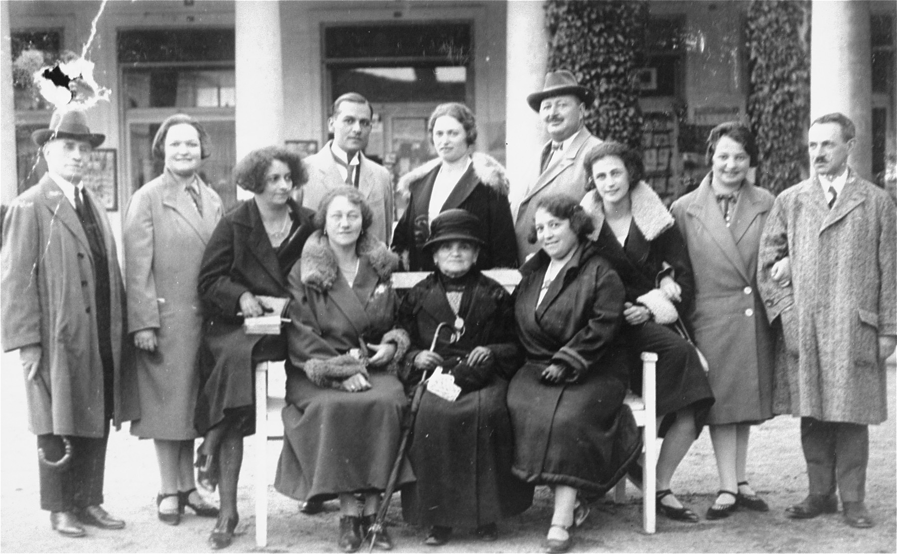 Group portrait of Jewish vacationers at a spa in Karlsbad, Czechoslovakia.    The donor, Magda Herzog Mueller, is pictured standing, second from the right.  Her sister, Julie, is standing, second from the left; her mother Lilly is seated on the bench at the right; her father, Jakub is standing behind Lilly.