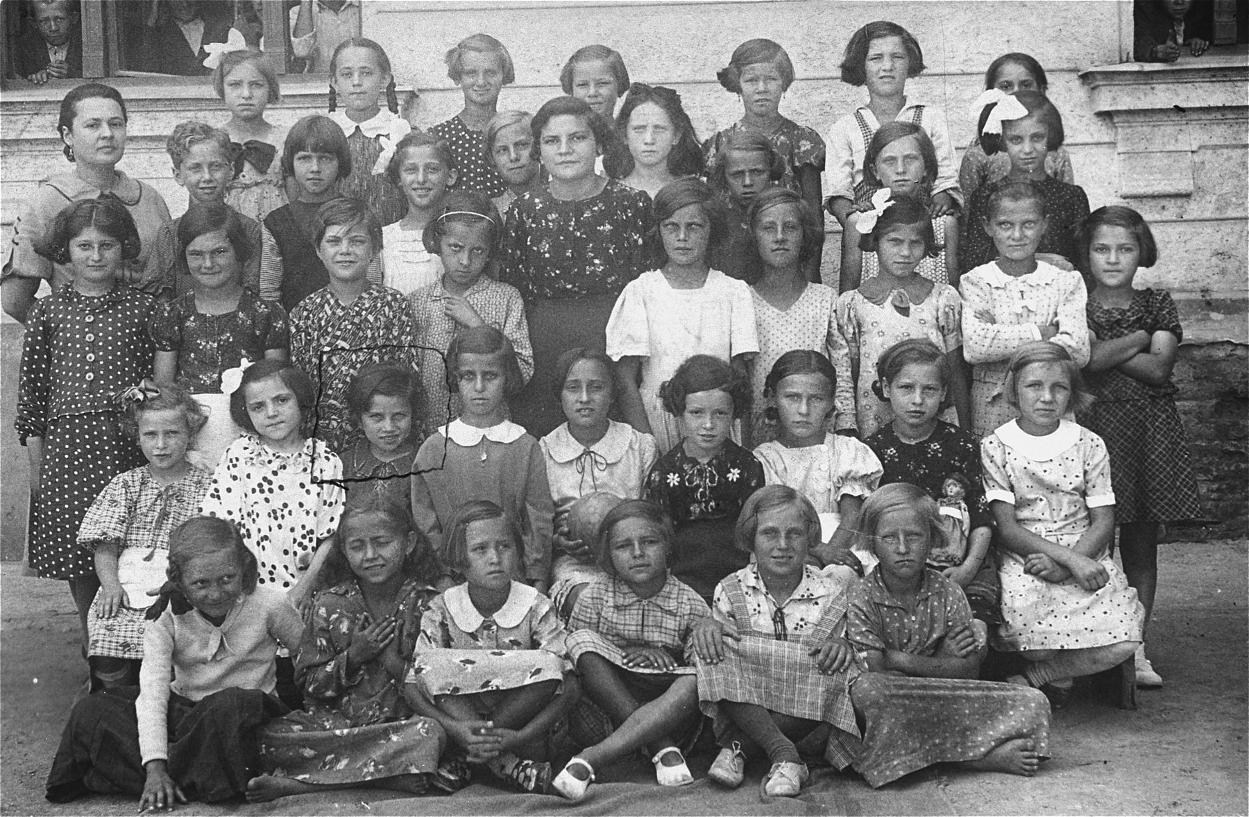 Group portrait of first grade students and teachers at a public school in Vinogradov, Ukraine.    Among those pictured is 6-year-old Edith Rottenstein (second row, third from the left).  Edith survived the Auschwitz and Stutthof concentration camps.