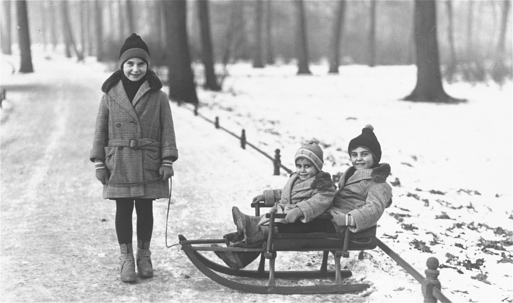 Three Jewish sisters sledding in the Berlin Tiergarten.  Pictured are Eva (standing), Hilde and Dodi Anker.