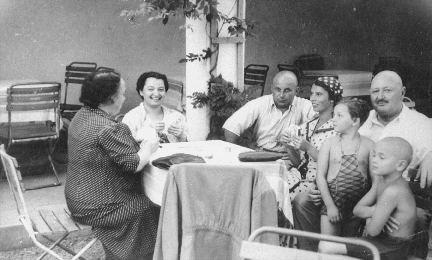 The Muller and Herzog families play cards at a resort hotel in Czechoslovakia.  Pictured at the far left are Lilly Herzog and the donor, Magda Herzog Muller; at the far right is Jakub Herzog with his two grandchildren, Alice and Heinrich.
