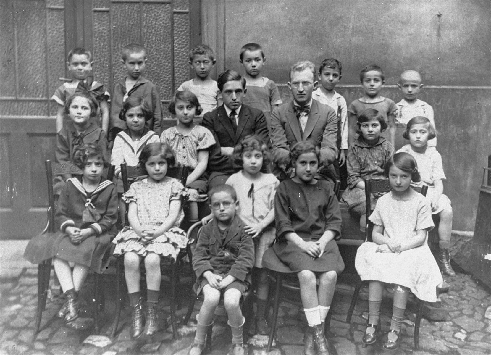 Group portrait of pupils at the Jiddvska Matice Skolska (founded by Viktor Kohn) taken on the first day of classes at the Jewish school.     Ruth Kohn is pictured at the right in the front row. The teachers are Oskar Quasnik Rabinowic (left) and Herman Furst (right).