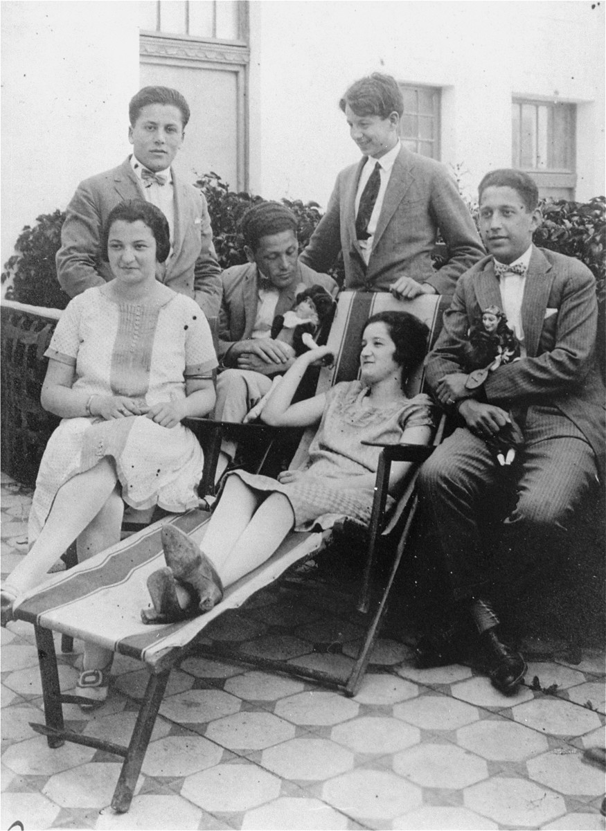 Jewish youth socialize on the patio of a private home in Hlohovec, Czechoslovakia.  The young women pictured are: Magda Mueller (left) and Emmy Rosenfeld; The young men (left to right) are: Imre Brody, Arpad Brody, Fritz Rosenfeld, and Irwin Brody.