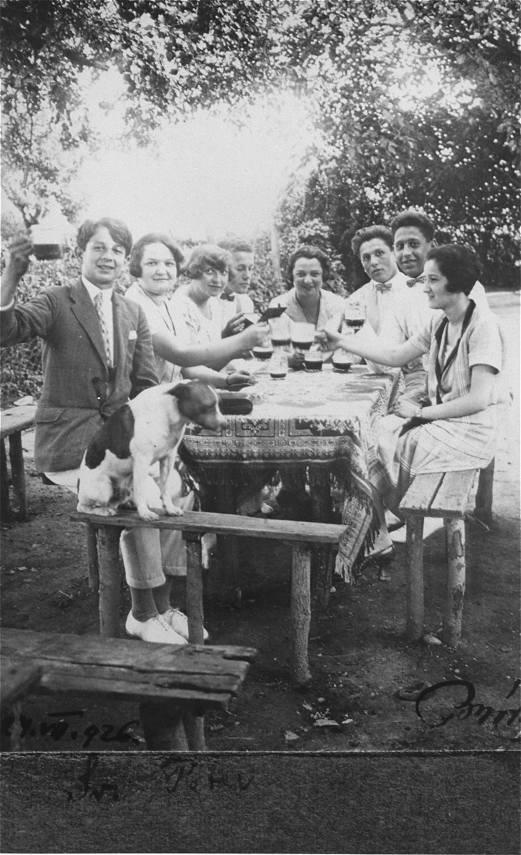 Jewish youth drink a toast at a garden party in Hlohovec, Czechoslovakia.  Pictured (from left to right around the table) are Fritz Rosenfeld, Julie Herzog, Bozsi Drechsler, Arpad Brody, Magda Herzog, Imre Brody, Irwin Brody, and Emmy Rosenfeld.