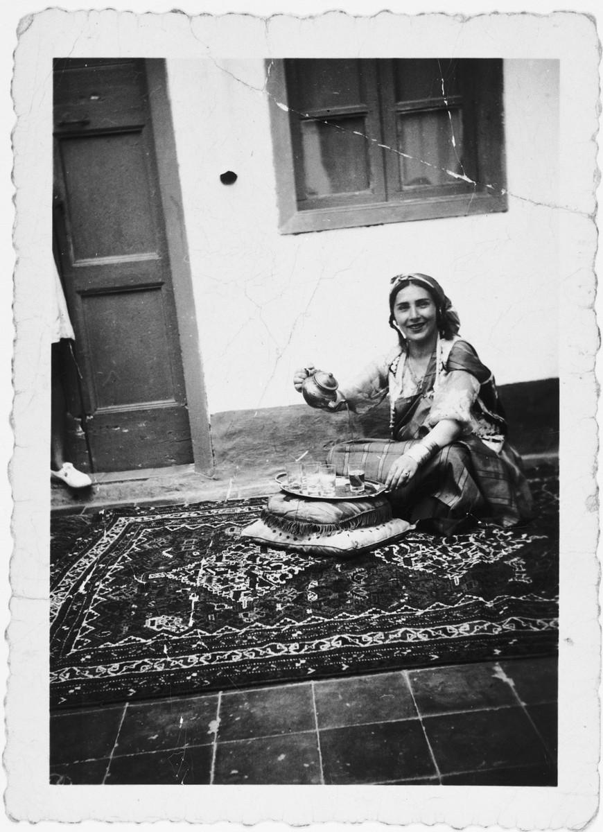 Irma Gruenberg serves coffee while seated on a rug in Benghazi, Libya.