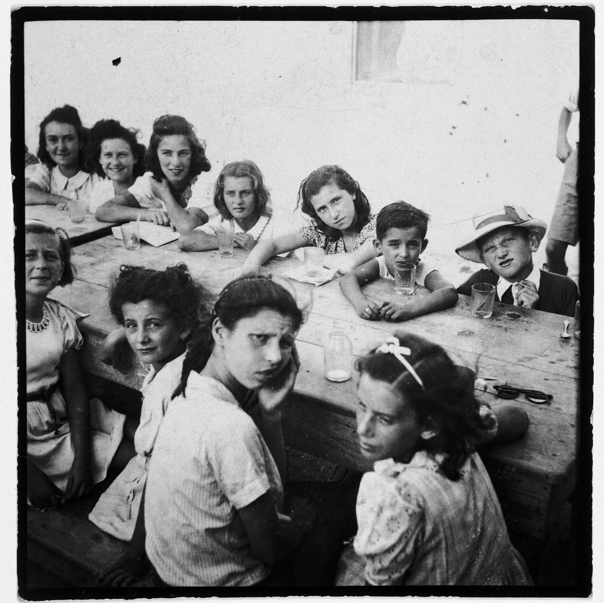 A group of children sits around a table in the Ferramonti internment camp.  Among those pictured is Walter Gruenberg.