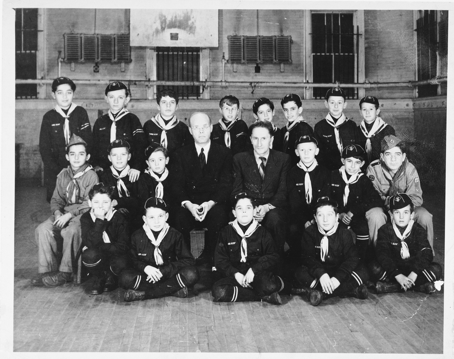 Children and leaders of a Fort Ontario cub scout troop.  Pictured in the front row (left to right) are Jakov Kampos, Wilhelm Wittenberg, Milan Polijokan, Silvestro Wachsmann, and Miko Finzi.    Pictured in the second row are Walter Grunberg, Nikola Marinkovic, Miroslav Lang, Mr. Lawrence, Ferdinand Kaska, Heinz Grun, Josef Hazan, and Erik Levy    Pictured in the third row are Branko Hochwald, Michael Hirt; Julius Krauthamer; possibly Jakov Levi, Walter Cohen, Pietri Albrecht, and two unidentified boys.