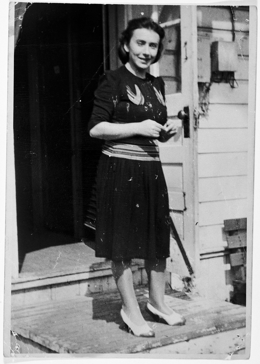 Irma Gruenberg stands at the entrace of a barracks in the Fort Ontario refugee center.