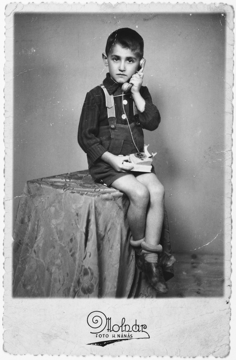 """Laszlo Ornstein poses for a studio portrait with a telephone less than two years before he was killed in Auschwitz.  The original caption, addressed to his father who was interned in a forced labor camp, reads """"I had called you, dear father to let you know that your children are waiting for you together with Jutka and Lacika""""."""