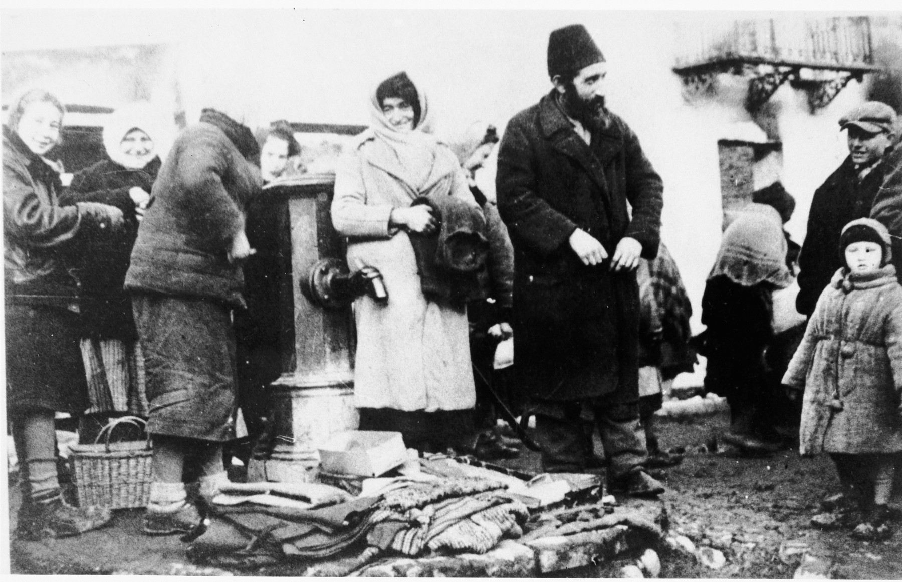 Jewish residents stand around a vendor's display of linen or clothing in the public square of an unidentified ghetto.