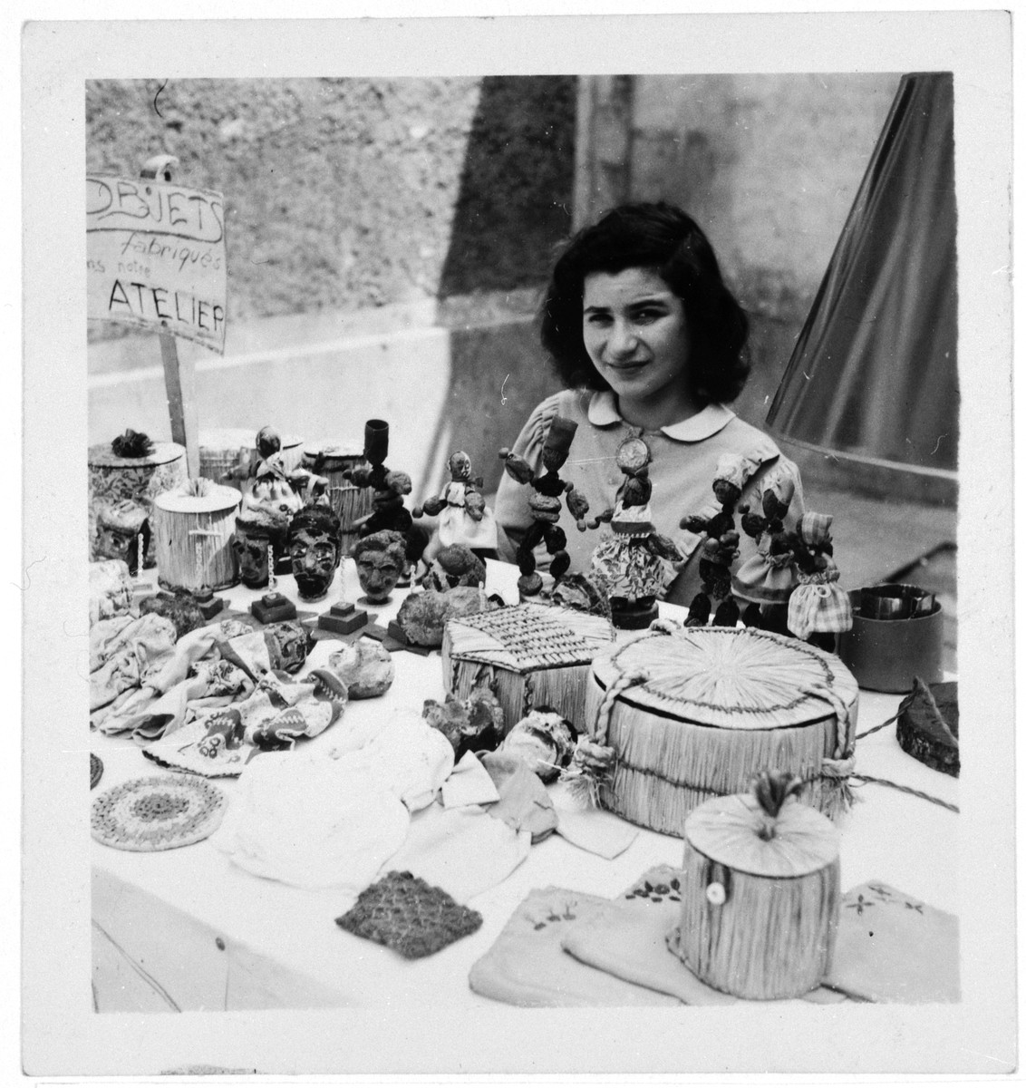 A young woman sits among a crafts exhibit in an OSE home, probably Draveil.